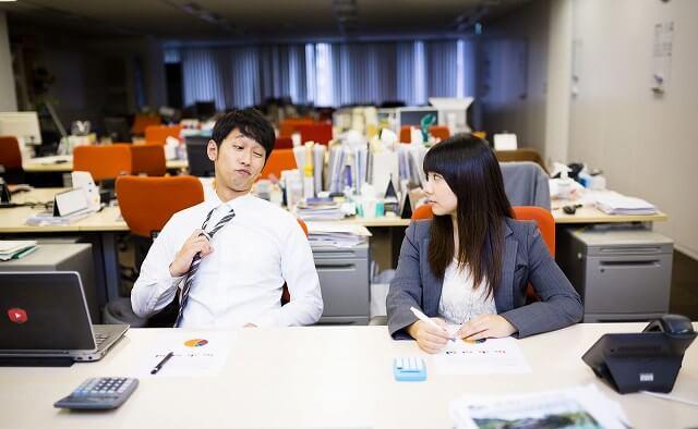 職場で話す男女の写真